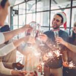 workers celebrating at a christmas party, this is one way to improve employee engagement this christmas.
